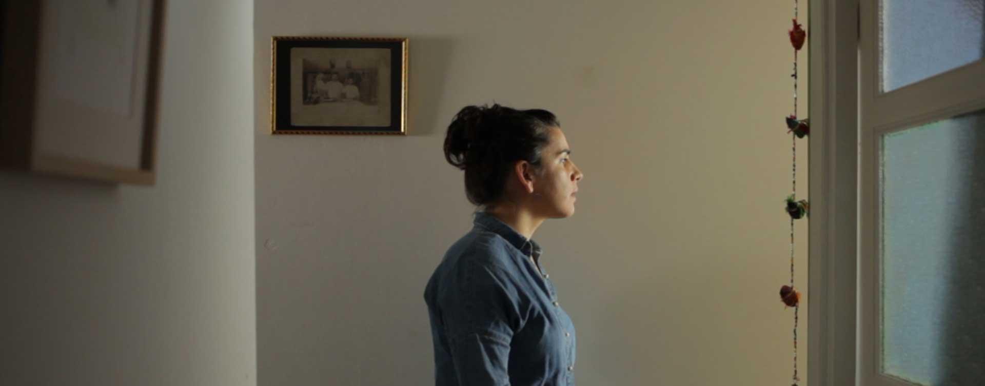 mujer mirando por la ventana de la habitación en el rodaje cinematográfico